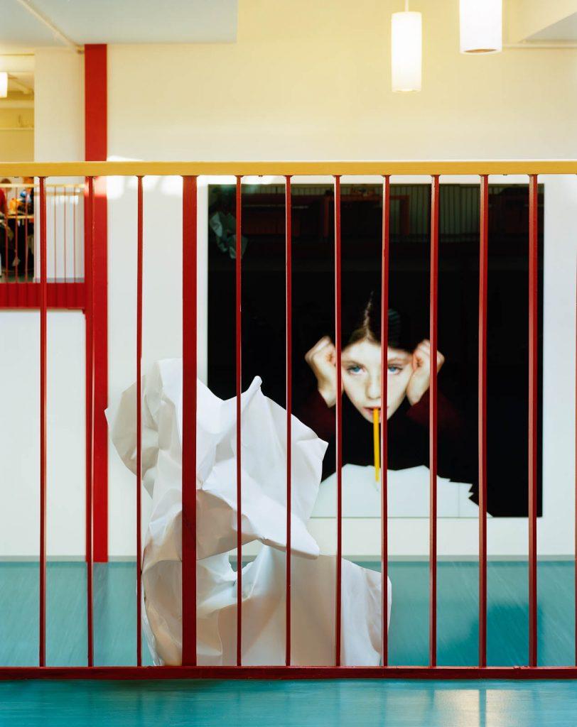 Verket fotograferat genom den röda pinnbalustraden på andra våningens balkong. Julia Peirone, Sharphead