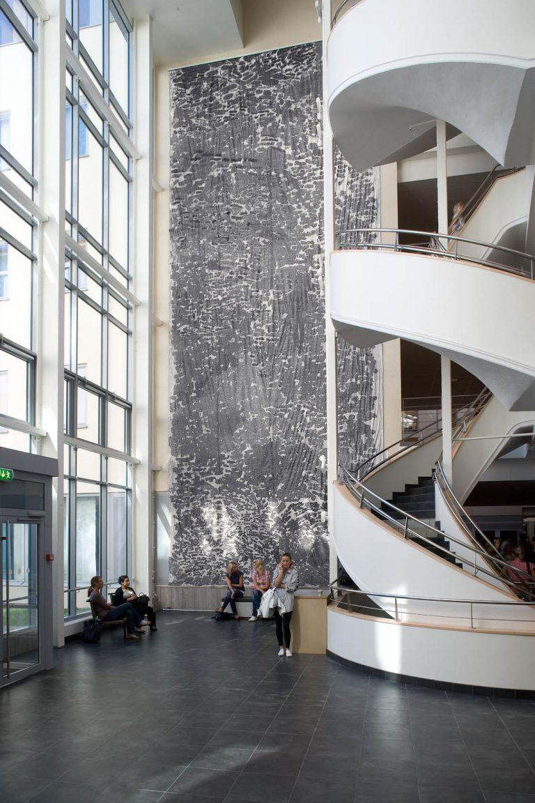 Mellan en vit vriden trappa och en yttervägg av glas hänger verket, flera våningar högt, i blyerts på vit grund. Zsuzsanna Gilice, pssst...