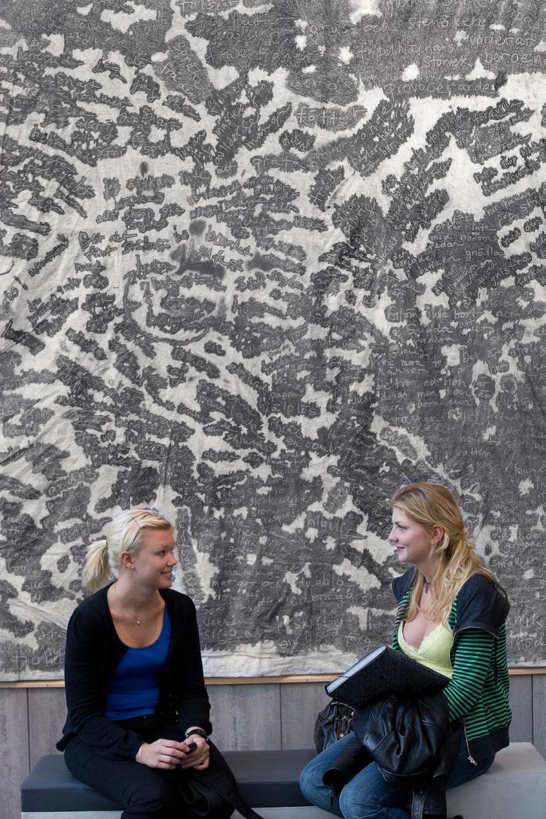Två kvinnor sitter på en bänk framför ett stort verk i blyerts som täcker väggen bakom dem. Verket är fyllt av ord, skrivna kors och tvärs. Zsuzsanna Gilice, pssst...