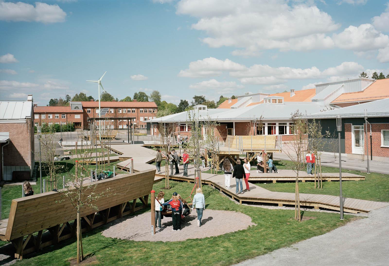 Skolgård med lekande barn, gångbroar av trä, vindsnurra. Marjetica Potrc och STEALTH, Fruit and Energy Farms in a Public Square.