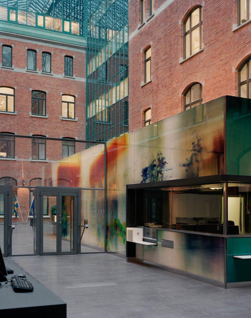 Tegelbyggnad med säkerhetsdörrar av glas in till gården och den skimrande disfärgade receptionsbyggnaden med abstrakta färgpartier i blått och rött. Nanna HŠänninen, Walks from dusk 'til dawn