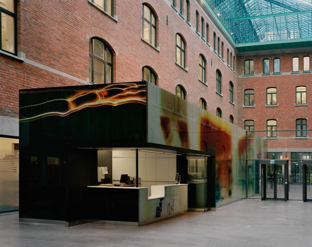 Fotografiet på receptionsbyggnadens kortsida liknar en blixt, medan långsidan har färgpartier som vagt påminner om huskroppar på en stadsgata. Nanna HŠänninen, Walks from dusk 'til dawn