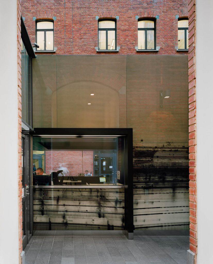 I receptionen sitter en man vid en dator. Receptionens glasfasad speglar svagt tegelbyggnaden framför. Nanna HŠänninen, Walks from dusk 'til dawn