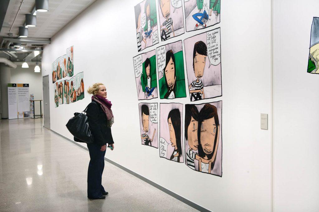En person står och läser på en vit vägg med serier. Daniel Novakovic, Jag tror jag är kär