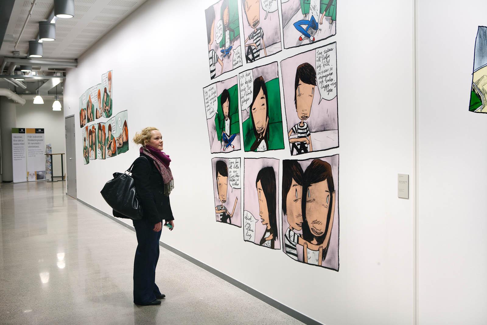 En person står och läser på en vit vägg med serier. Daniel Novakovic, Jag tror jag är kär.
