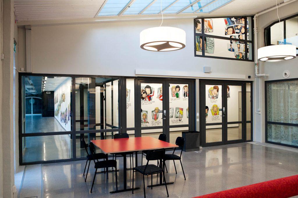 Ett klassrum. Genom glasväggen syns korridorer med seriestrippar på väggarna. Daniel Novakovic, Jag tror jag är kär