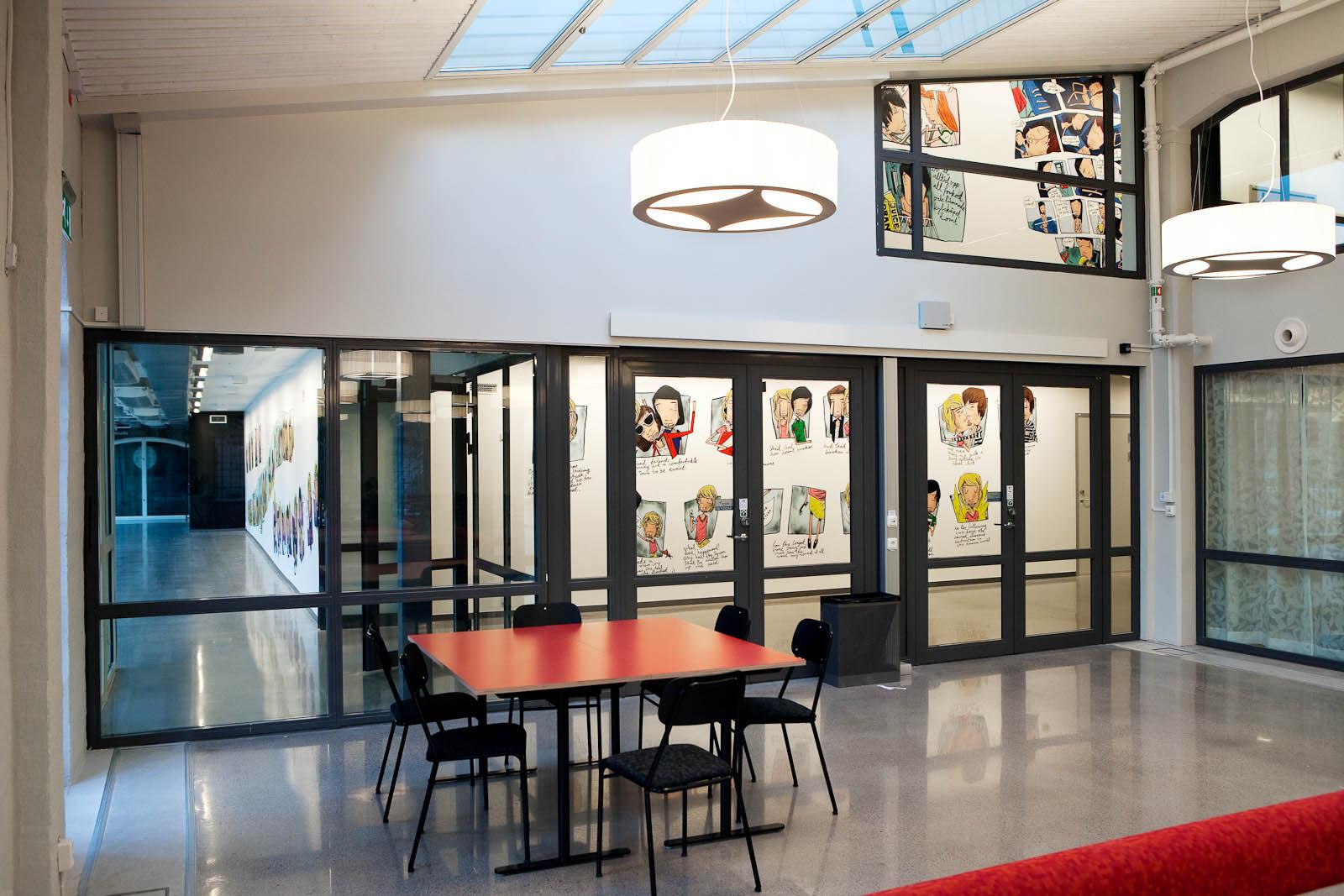 Ett klassrum. Genom glasväggen syns korridorer med seriestrippar på väggarna. Daniel Novakovic, Jag tror jag är kär.