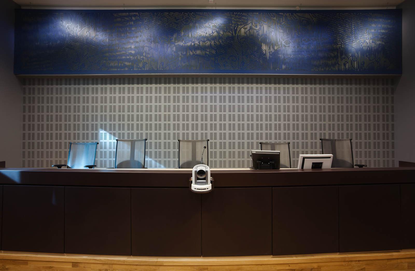 Panel på väggen ovanför domarbordet. Blått med utskurna mönster. May Bente Aronsen, Lyssnande vägg