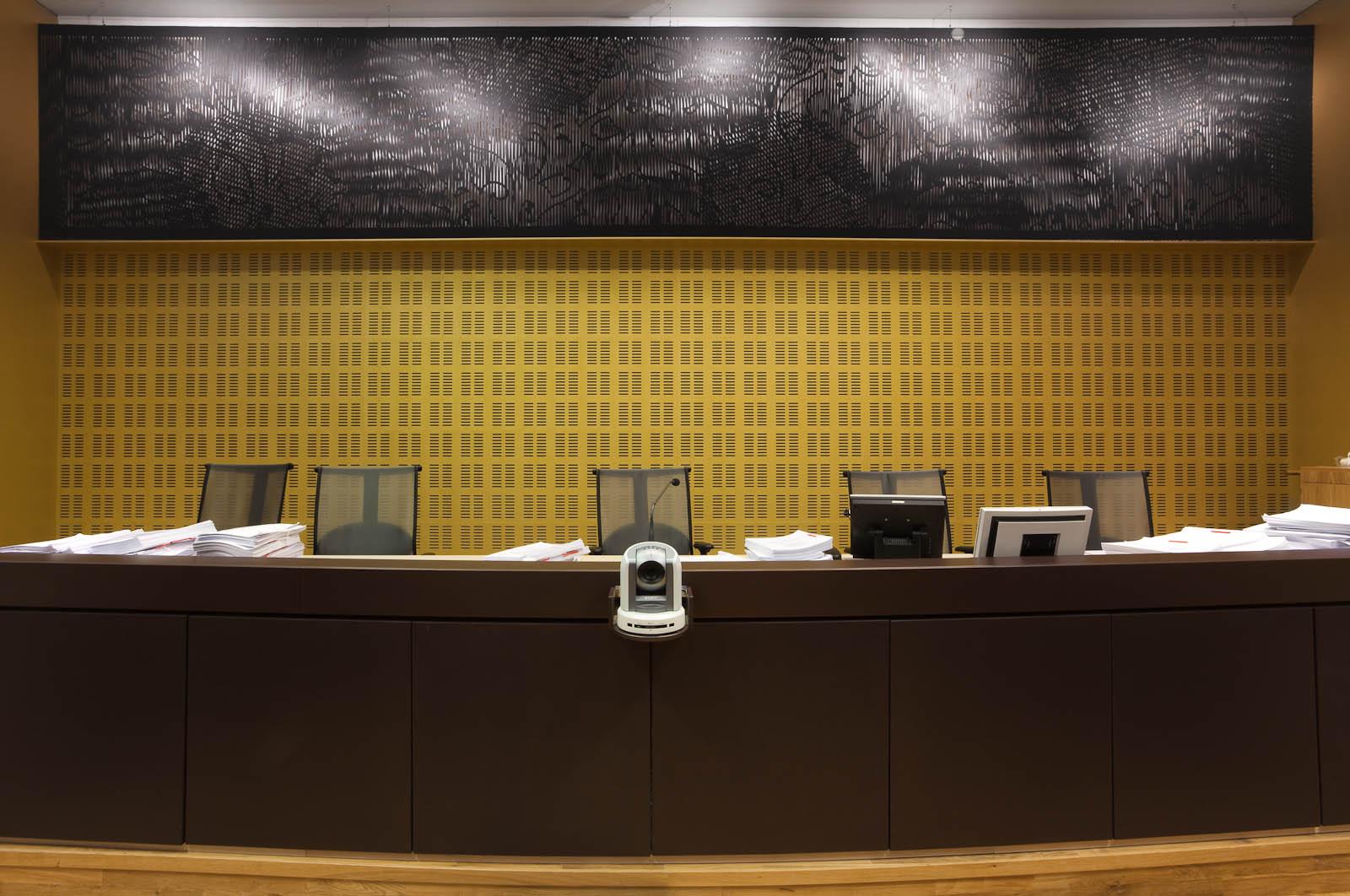 Panel på väggen ovanför domarbordet. Svart med utskuret mönster. May Bente Aronsen, Lyssnande vägg