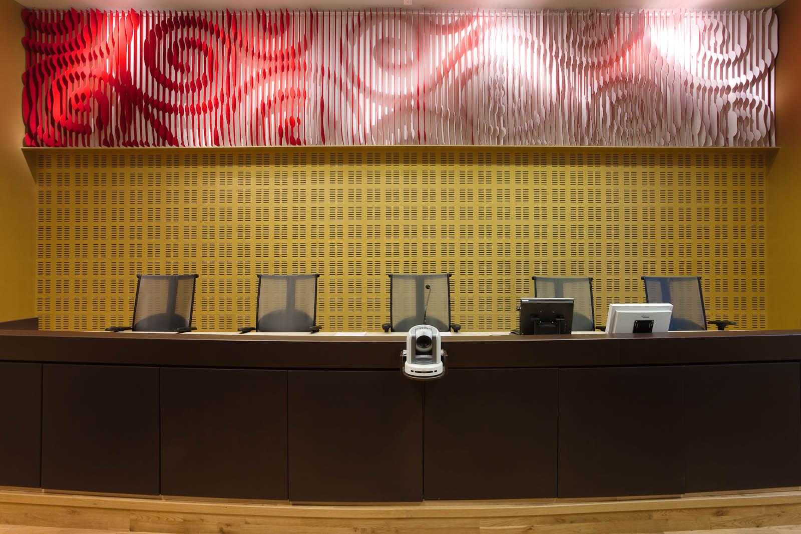 Panel på väggen ovanför domarbordet. Röd-vitt med utskurna spiralliknande mönster. May Bente Aronsen, Lyssnande vägg