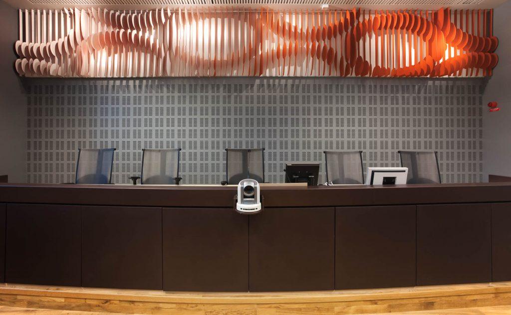 Panel på väggen ovanför domarbordet. Orange-vitt med utskurna cirkel- och vågmönster. May Bente Aronsen, Lyssnande vägg