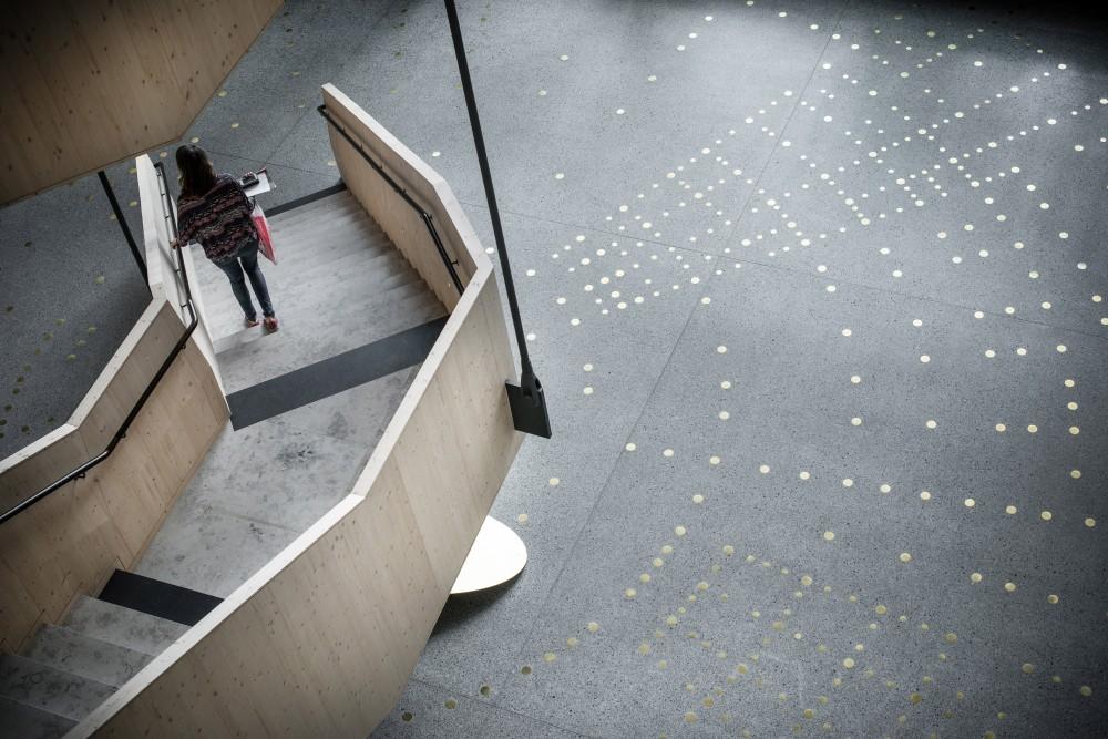 Reflekterande mässingspunkter i ett mönster, ingjutna i ett terrazzogolv, bredvid en trätrappa. Sophie Tottie, P.ULL