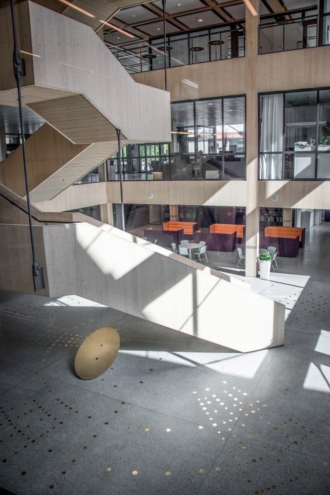 Reflekterande mässingspunkter i ett mönster, ingjutna i ett terrazzogolv, bredvid en trätrappa. I bakgrunden sittgrupper. Sophie Tottie, P.ULL