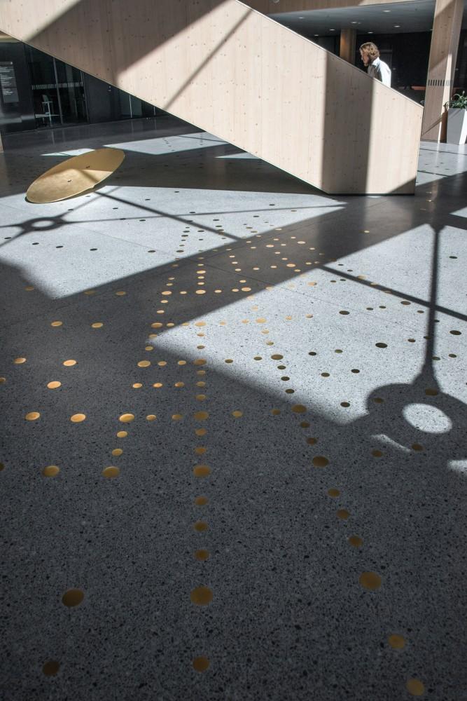 Reflekterande mässingspunkter i ett mönster, ingjutna i ett terrazzogolv, bredvid en trappa av trä. Sophie Tottie, P.ULL
