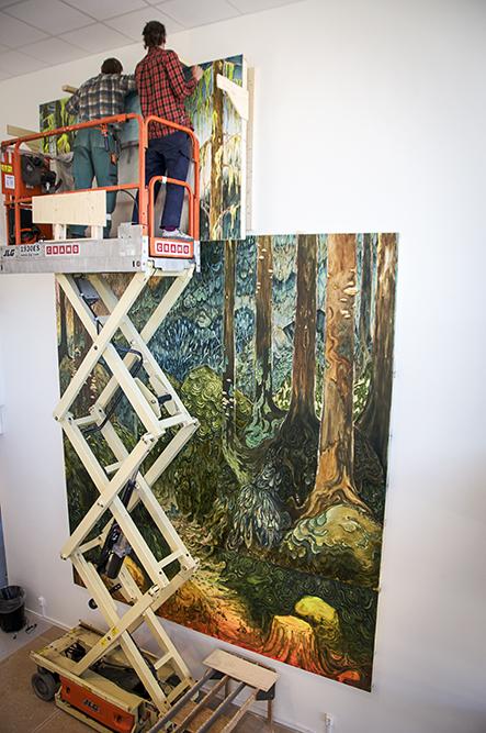 Två män med bygghjälmar i en skylift monterar överdelen av målningen på väggen. Danilo Stankovic, När fåglar tystna.