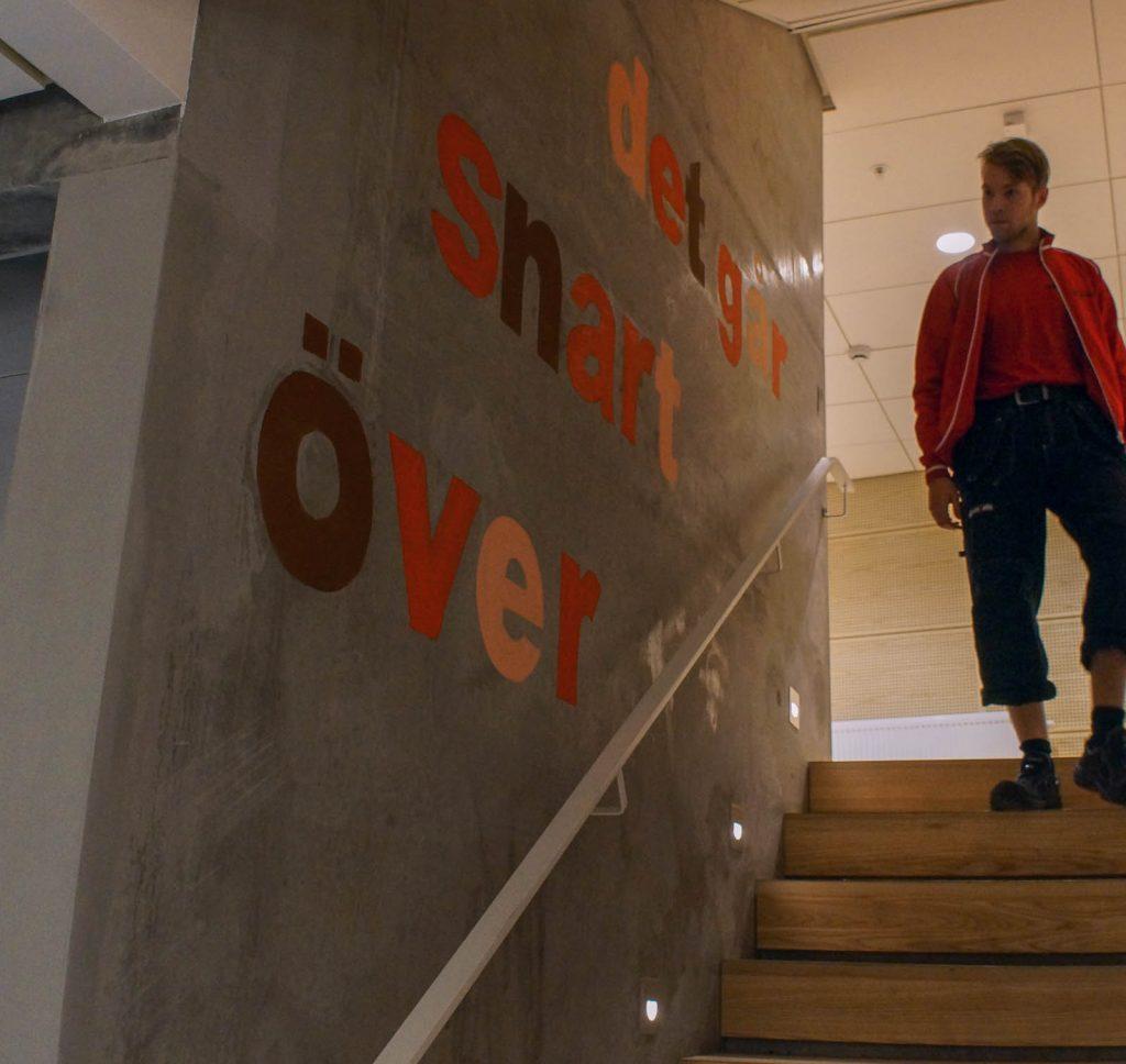 """Betongvägg med ett trappräcke och olikfärgade bokstäver som bildar texten: """"Det går snart över."""" Annika Ström, men vänta nu, 2014"""