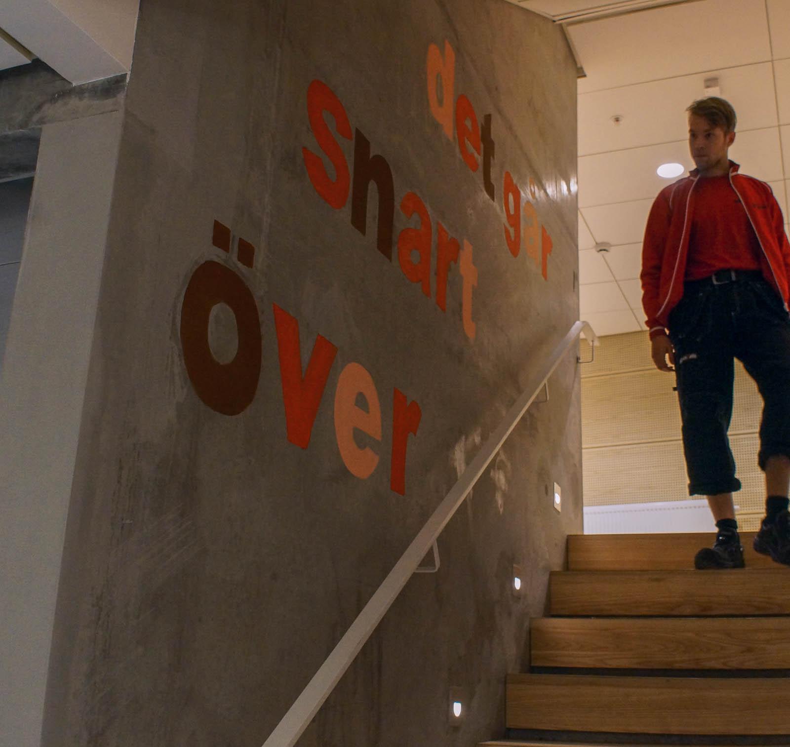 """Betongvägg med ett trappräcke och olikfärgade bokstäver som bildar texten: """"Det går snart över."""" Annika Ström, men vänta nu, 2014."""