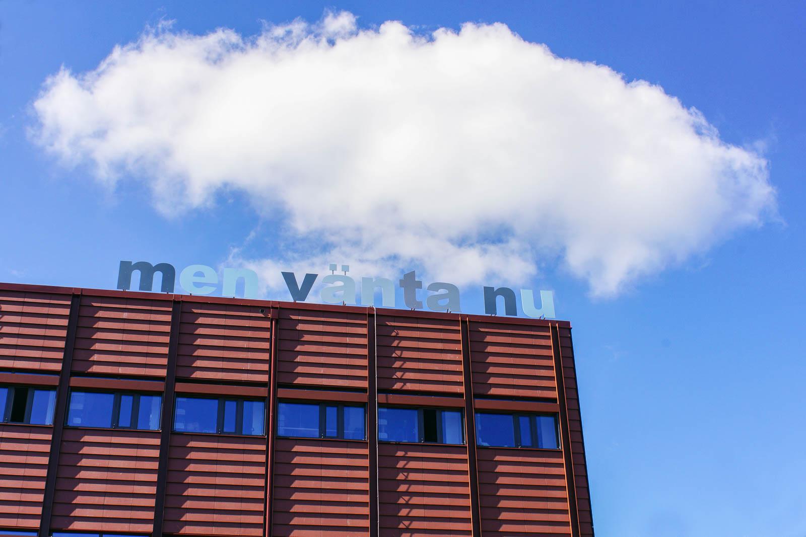 """Ett rött flervåningshus. På taket avtecknar sig mot himlen bokstäver i skiftande nyanser av blått. Det står: """"Men vänta nu"""". Annika Ström, men vänta nu, 2014."""