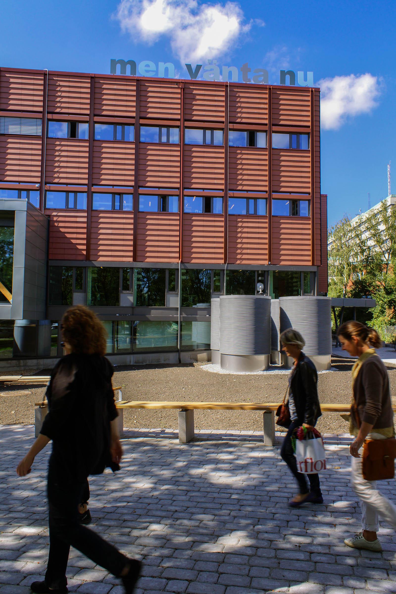 """Ett rött flervåningshus. På taket avtecknar sig mot himlen bokstäver i skiftande nyanser av blått: """"Men vänta nu"""". I förgrunden folk som går framför huset. Annika Ström, men vänta nu, 2014."""