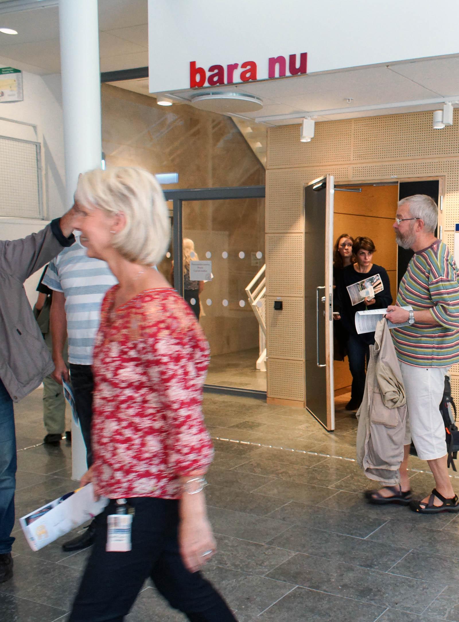 """Människor i en korridor och på väg ut ur ett trapphus. På den vita väggen ovanför dörren står med röda bokstäver orden: """"bara nu"""". Annika Ström, men vänta nu, 2014."""