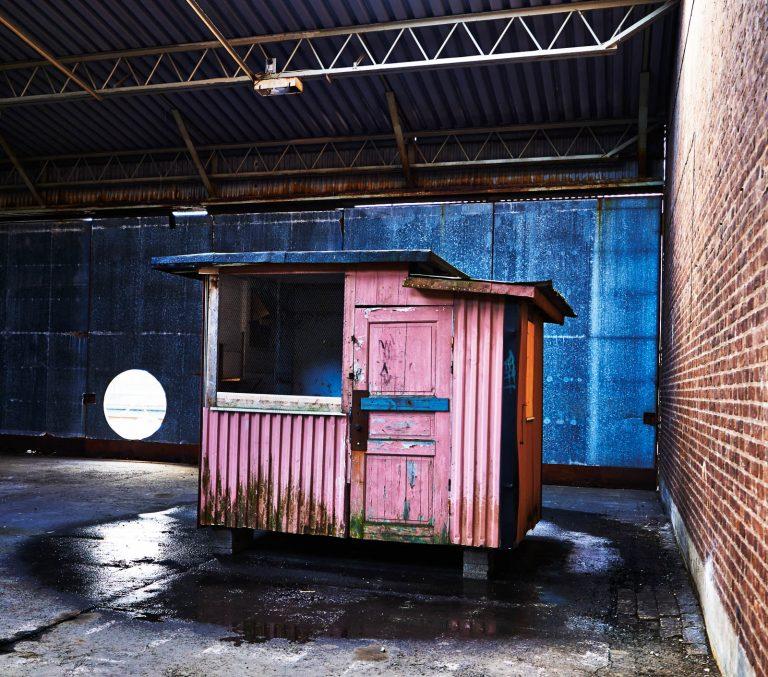 Slitet duvslag av trä, står i en byggnad av tegel och korrugerad plåt. Simon Starling, Loft Lift.