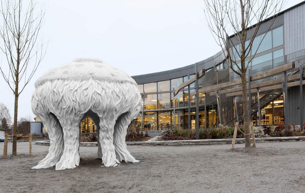 Skulpturen Tereuma står utanför ett upplyst bibliotek med stora glaspartier. Cecilia Ömalm Krajcikova, Tereuma (2012)
