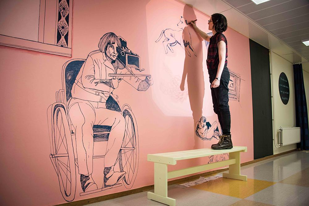 Konstnär Gerd Aurell står på en träpall och tecknar på väggen. Hon har avslutat en teckning av en man i rullstol med en märklig kikare vid ögat. Till mitten hunnen.