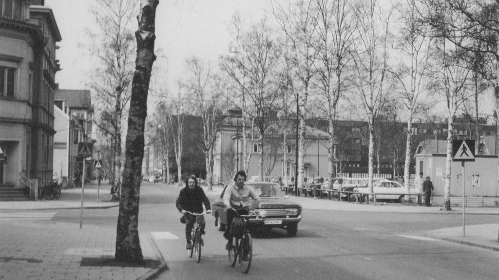 Svartvit bild från 1970-talet. Cyklister och bil i en korsning. I bakgrunden träd, hus och parkering.