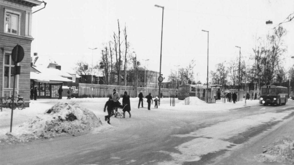 Svartvit bild från 1970-talet. Människor går längs en snöig trottoar. I bakgrunden en buss som kör in mot en busskur.