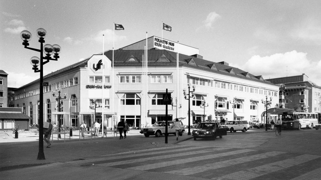 Svartvit bild från 1970-talet. Flaggor vajar på köpcentret vid Vasaplan. En buss och bilar släpper av folk. Människor går längs trottoaren.