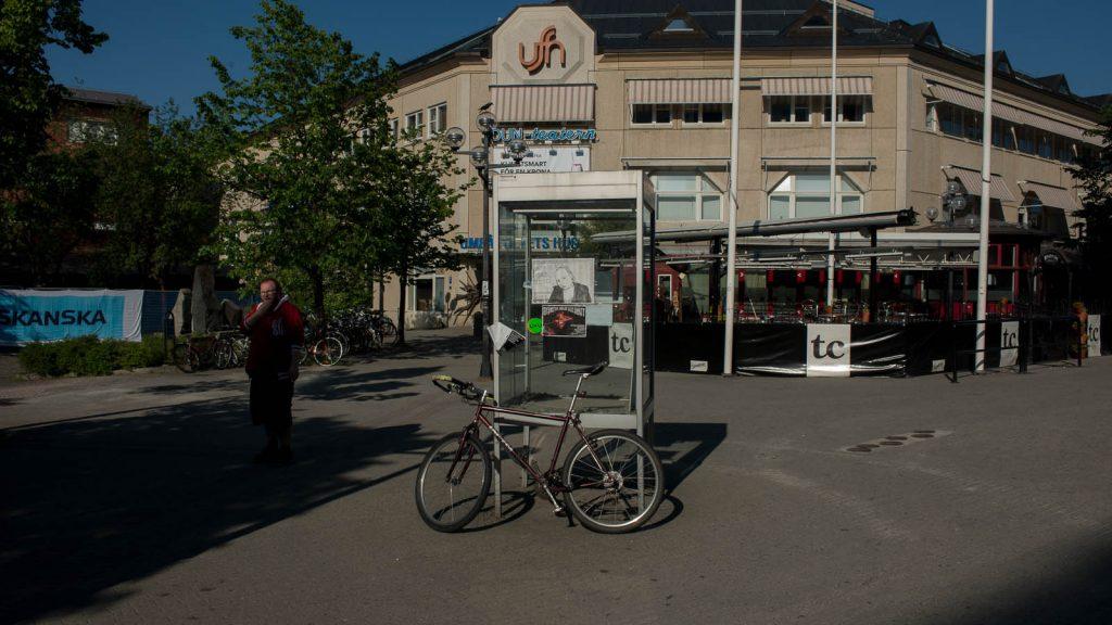 Cykel framför en gammal telefonkiosk. I bakgrunden köpcentrum och en uteservering. Vasaplan i Umeå, 2013