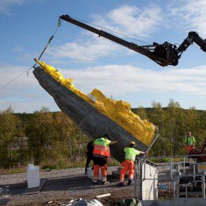 Skulpturen på plats vid Ädnamvaare i Kiruna. Den lyfts i lodrätt läge med hjälp av noggrann koordinering, kranbil och muskelkraft.