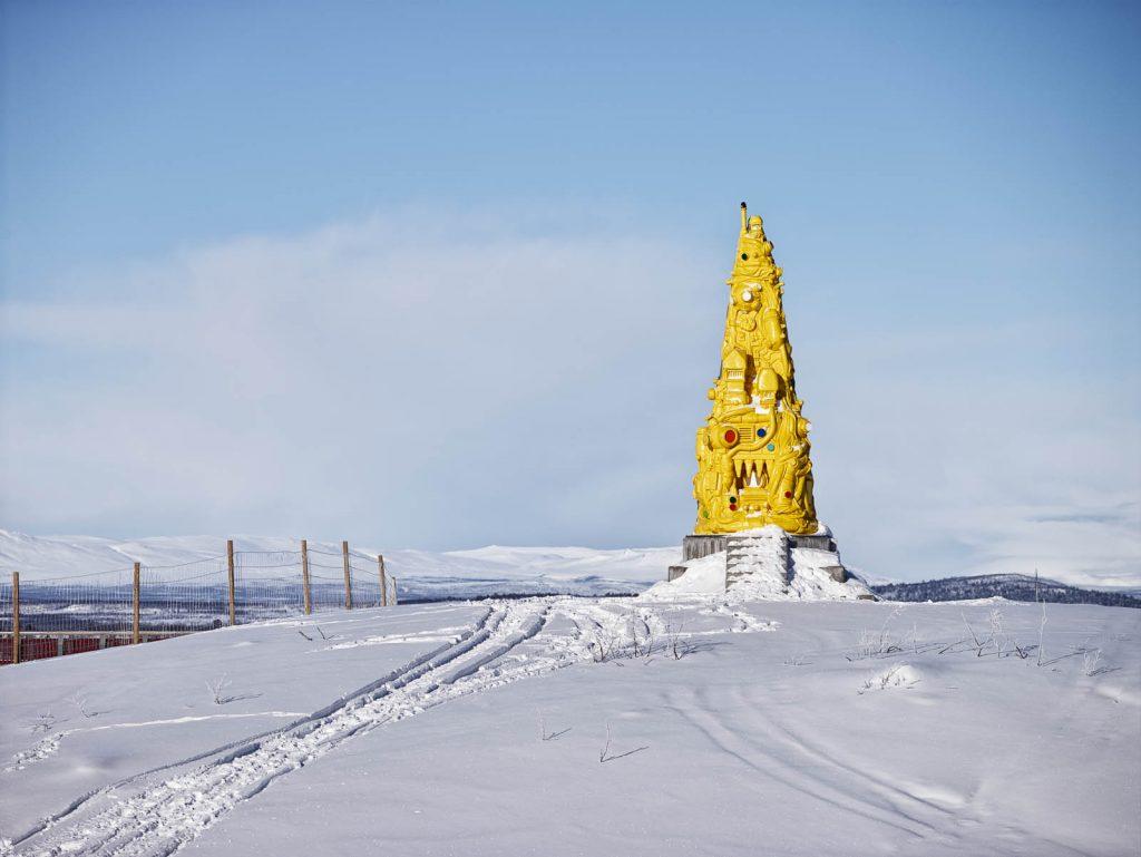 Skulpturen Totems gula sida, med något som ser ut som byggnader, taggar och i toppen det som tycks vara en hjälmklädd figur med höjd näve. Oskar Aglert, Totem