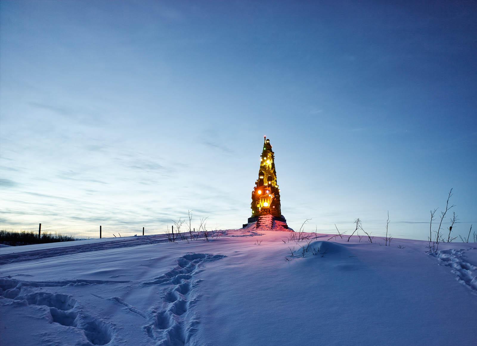 I ett snötäckt landskap lyser skulpturenen Totem av Oskar Aglert i olika färger.