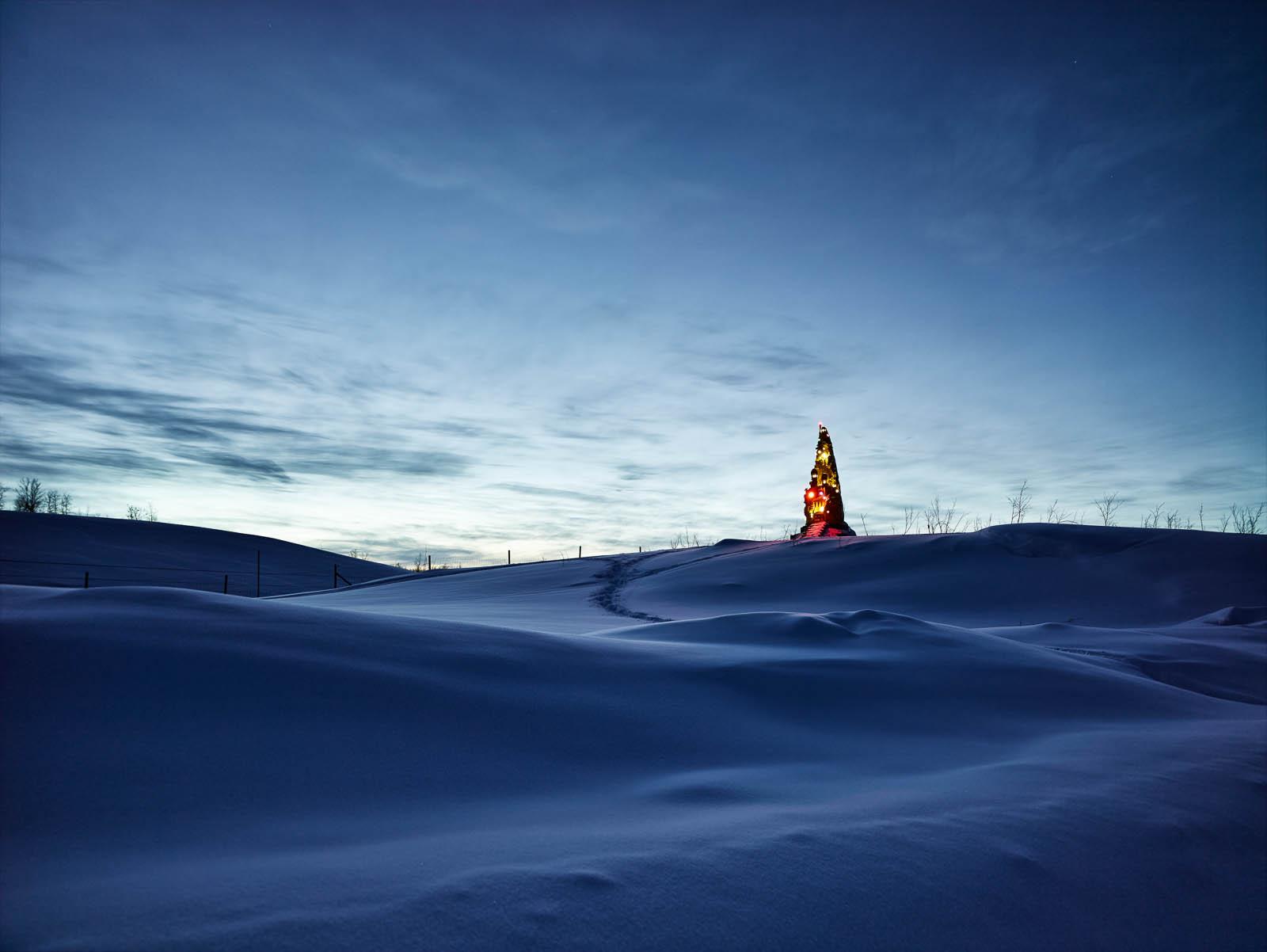 Natthimmel. Snölandskap. På avstånd lyser och glittrar Totem på sin kulle. Oskar Aglert, Totem.