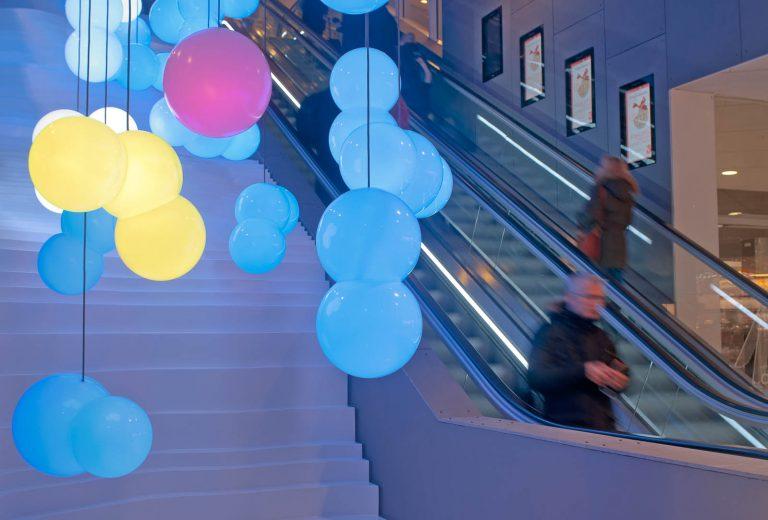 Hängande blå och gula lampor samt en röd. I bakgrunden en rulltrappa. Bigert & Bergström, Morgondagens Väder, 2012.