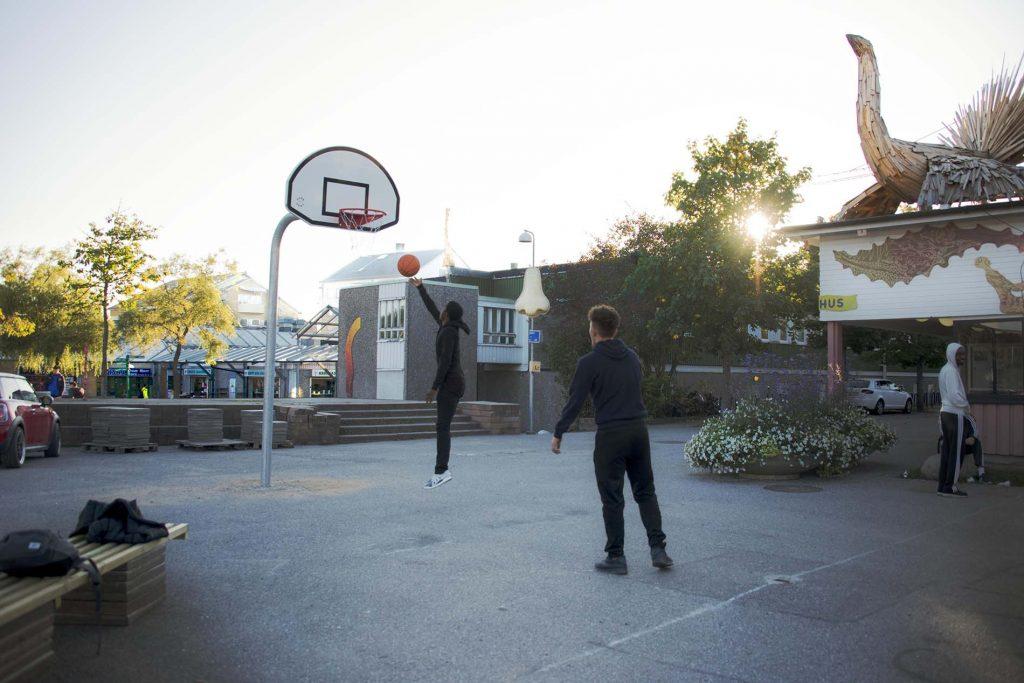 En pojke hoppar upp i luften för att kasta en basketboll i korgen, en kille står snett bakom närmare kameran. Det är en asfaltsplan utanför ungdomsgården tillika kulturhuset i Jordbro.