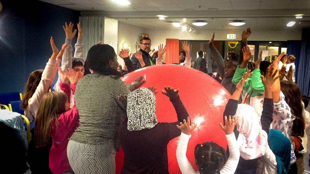 Barn och vuxna står runt en stor röd boll.
