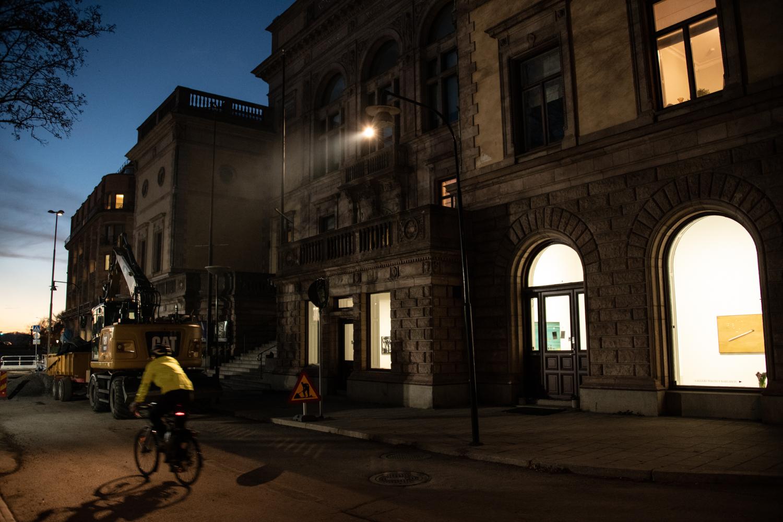 På fasaden till Konstakademien i Stockholm lyser lampan från verket Förhandlingen.