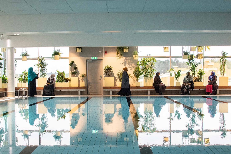 Kvinnor som rör sig längs kanten av, och speglas i, en pool framför krukväxter och stora fönster.