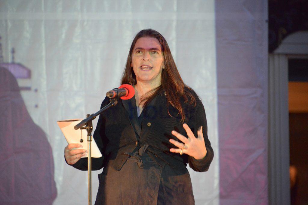 En person står i projektorljus och talar i mikrofon och ett block i ena handen.