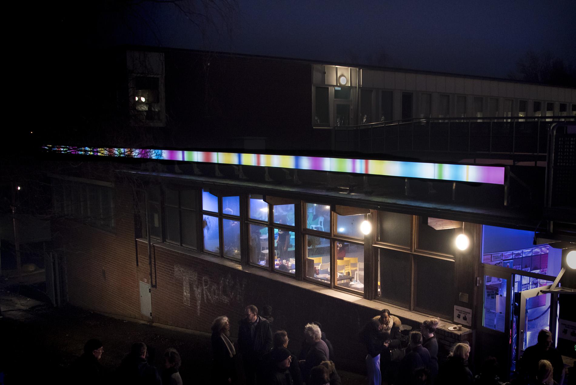 En långsmal ljusbox i olika färger. Ljuslinjen är tänd och det är kväll.