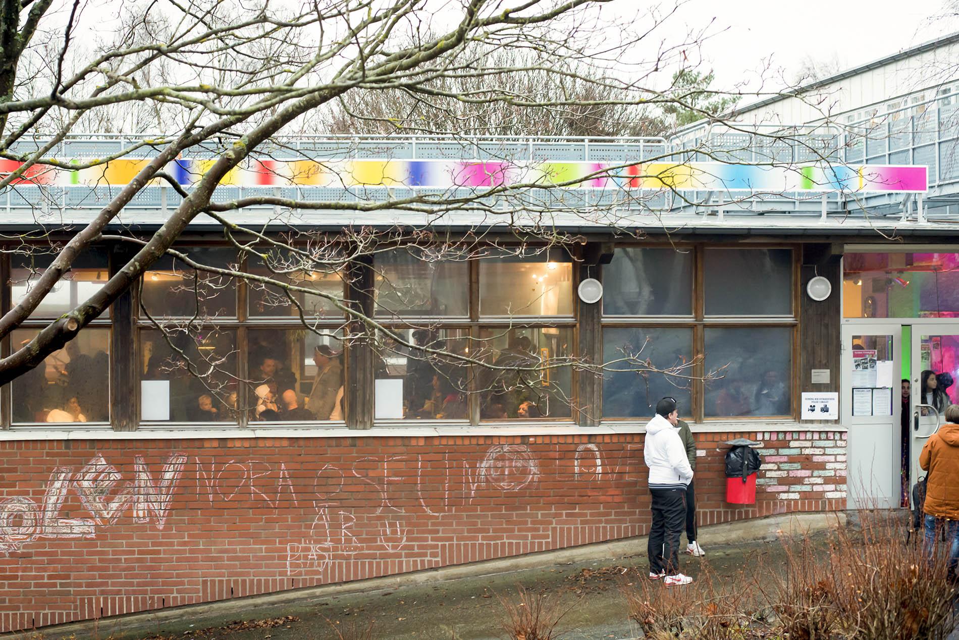 En linje av ljusboxar i skiftande färger löper längs med en tegelbyggnad, det är dag och ljuslinjen är släckt.