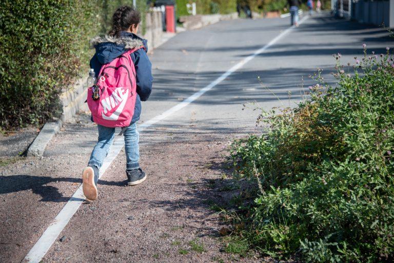 Flicka med ryggsäck går längs en vit linje i marken