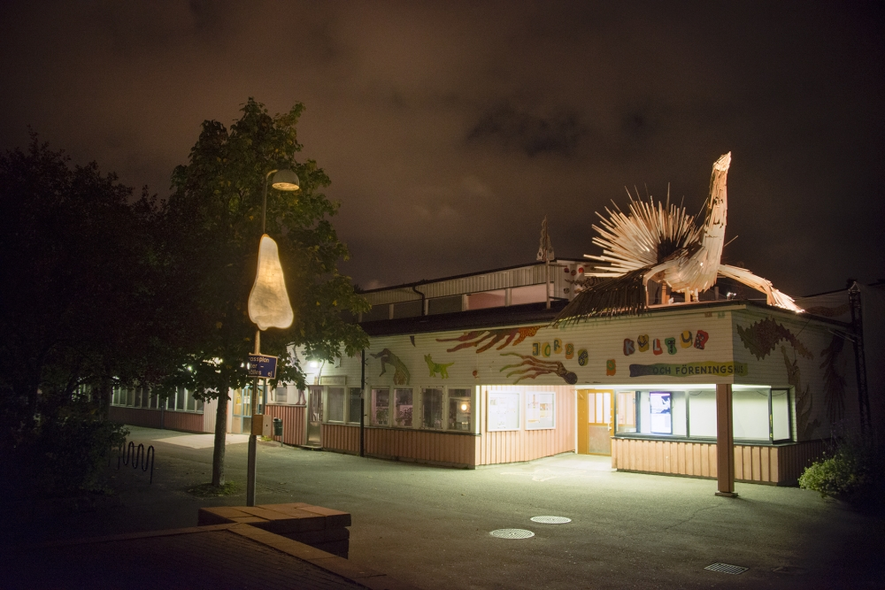 En lysande näsa på en lyktstolpe till vänster i bild och en belyst fågel på taket till kulturhuset i Jordbro. Det är kväll..