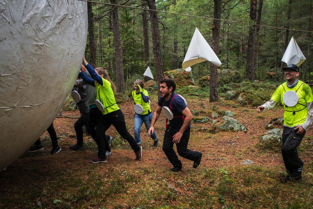 Människor i en skog rullar en stor boll.