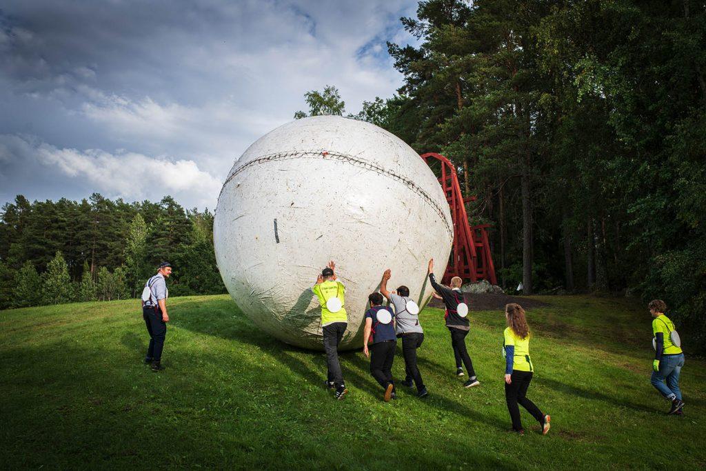 En stor boll rullas uppför en backe.