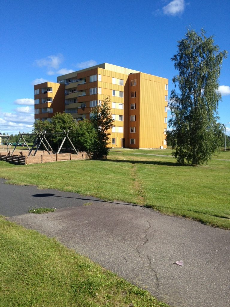 Gult flerfamiljshus på en gräsmatta. Gungor i närheten.