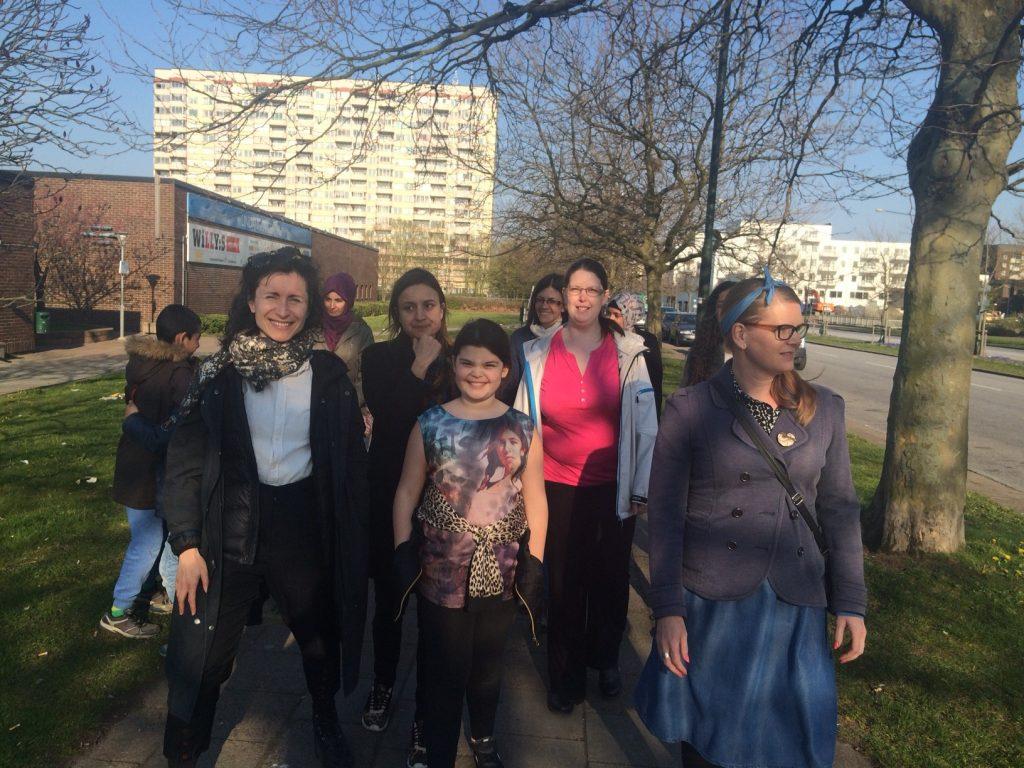 En grupp kvinnor i olika åldrar står i ett bostadsområde. Några tittar på kameran och ler.