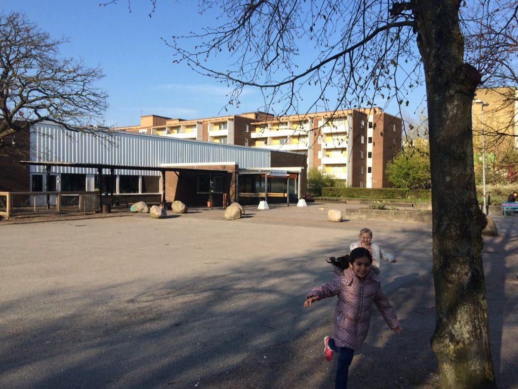 Två flickor springer skrattande över en skolgård. I bakgrunden bostadshus.